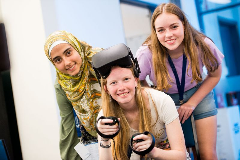 Three students posing with an Oculus Rift headset
