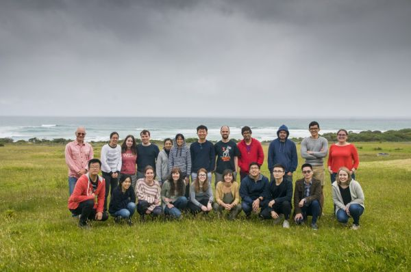A group photo of the Kent lab, taken in a green field with a view of the ocean on an overcast day